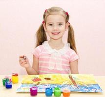 süßes lächelndes kleines Mädchen, das mit Farbe und Pinsel zeichnet foto
