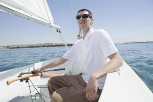 Mann segelt auf Segelboot foto