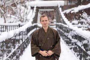 Mann, der traditionelle japanische Yukata während des Winterschnees trägt foto