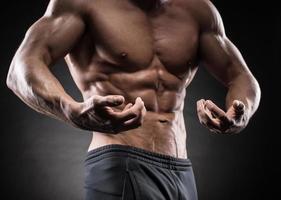 muskulöser Kerl auf schwarzem Hintergrund foto