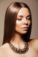 schöne Frau mit perfektem Make-up, das Schmuck trägt foto