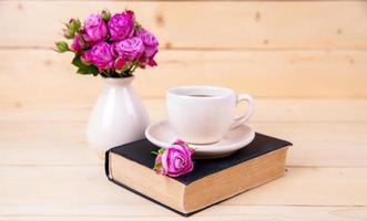 schöner Rosenstrauß in Vase. Buch, Blumen foto
