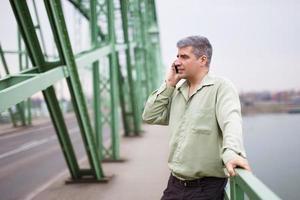 junger Unternehmer ruft an der Brücke foto