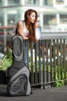 junge schöne Frau, die draußen mit ihrer Gitarrengig-Tasche aufwirft