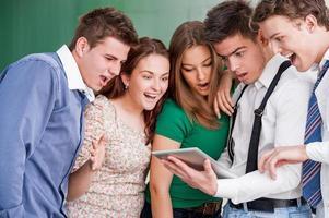 Studenten, die auf ein Tablet schauen foto