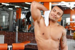Mann wischte sich mit Handtuch im Fitnessstudio foto