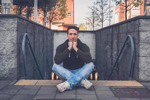junger Mann, der in einem städtischen Kontext aufwirft foto