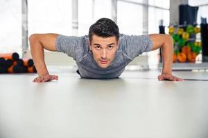 gutaussehender Mann, der Liegestütze im Fitnessstudio tut foto