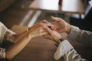 Frau und Mann Händchen haltend in der Kaffeebar. foto