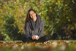 Herbst im Park, junge lächelnde Frau, die in der Natur entspannt foto