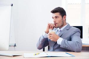 Geschäftsmann im Anzug, der Eiskaffee mit Stroh trinkt foto