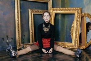 Schönheit reiche brünette Frau im Luxusinnenraum nahe leeren Rahmen, foto