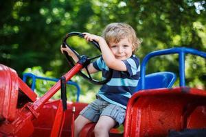 Porträt des kleinen blonden Jungen im Traktorsommer foto