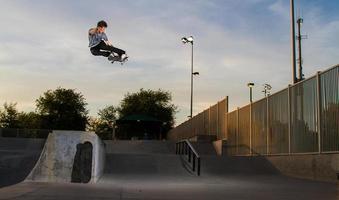 Skateboarder macht einen Trick in der Luft foto