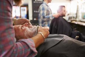 männlicher Friseur, der Klienten für Rasur im Laden vorbereitet foto