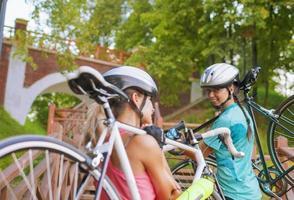 Zwei kaukasische Sportlerinnen trainieren mit Fahrrädern foto