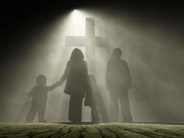 hinterleuchtete Menschen, die vor einem christlichen Kreuz stehen foto