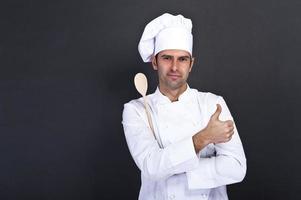 Porträt des Kochs mit Löffel über dunklem Hintergrund foto