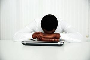 afrikanischer Mann, der an seinem Arbeitsplatz schläft foto
