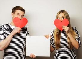 glückliches Paar, das weiße leere und rote Herzen hält. foto