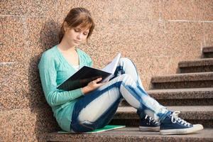 Mädchen sitzt auf Treppen und liest Notiz foto