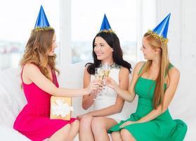 Drei Frauen tragen Hüte mit Champagnergläsern foto