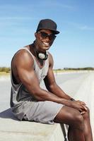 glücklicher junger afrikanischer Mann, der auf einer Promenade sitzt foto