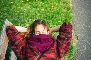 Frau, die auf einer Bank im Park schläft foto