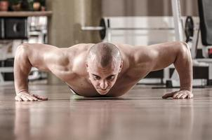muskulöser Mann, der Liegestütze macht foto
