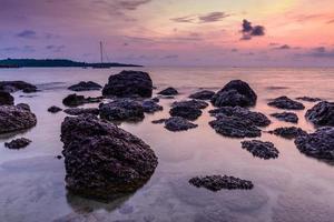 Seestück mit Stein bei Sonnenaufgang.