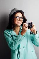 schönes Mädchen in einem Hut mit Kamera.