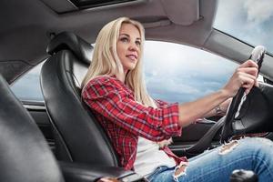 junge Blondine fahren ein Auto foto