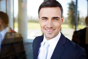 glücklicher hübscher Geschäftsmann im Anzug foto