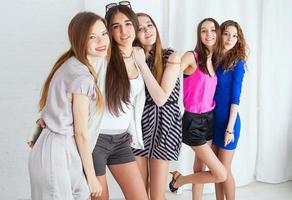 Fünf schöne Mädchen plaudern und lachen in der Nähe der weißen Wand foto