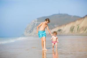 zwei Kinder, Bruder und kleine Schwester, laufen am schönen Strand