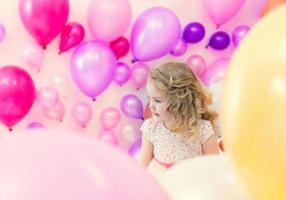 hübsches Mädchen posiert im Studio, wo viele Luftballons