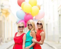 schöne Mädchen mit bunten Luftballons in der Stadt foto