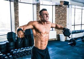 muskulöser Mann, der Hanteln hebt foto