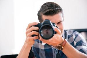 Mann, der mit Fotokamera schießt foto
