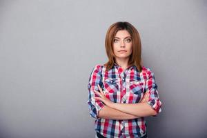 junge Frau stehend mit verschränkten Armen foto