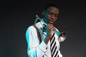 Retro Afroamerikaner Jazzmusiker hält seine Trompete. foto