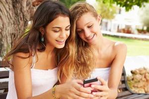 zwei Teenager-Mädchen, die Handy verwenden, das auf Parkbank sitzt foto
