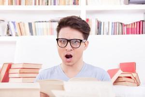 verwirrter Student mit Brille, umgeben von Büchern