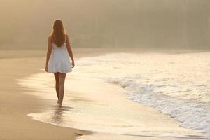 Frau, die auf dem Sand des Strandes geht foto