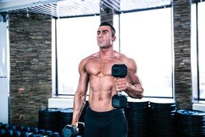 muskulöses Manntraining mit Hanteln foto