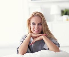 junge schöne Frau, die auf Couch in ihrem Zimmer sitzt foto