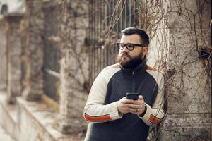 Mann mit Bart und Brille hält Handy SMS im Freien