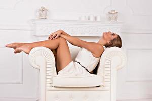 junges blondes schönes Mädchen, das auf einem weißen Cou sitzt foto