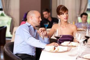 Paar flirtet am Restauranttisch foto