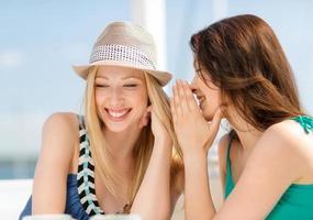 zwei Mädchen flüstern in einem Café und lächeln